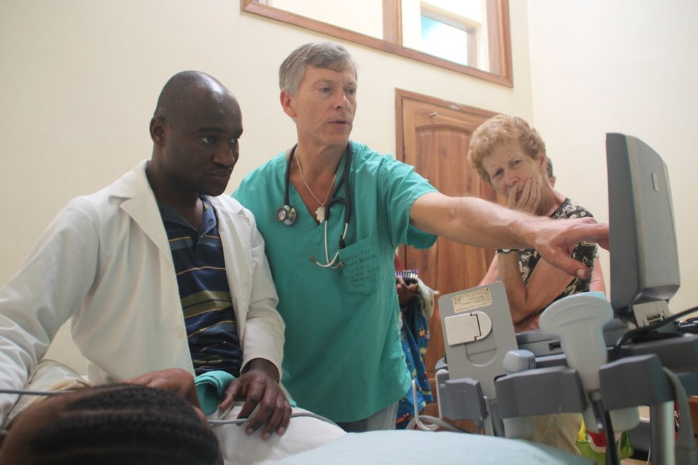 Dr Gabriel Kissima and volunteer cardiologist Dr Reed Shnider performing a heart echo on Beatrice