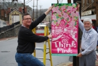 Randy Neely, owner of the Good Life Market and Ed Lilley, President of the Ellicott City Restoration Foundation hang one of the new THINK PINK banners on Main Street in between April showers.