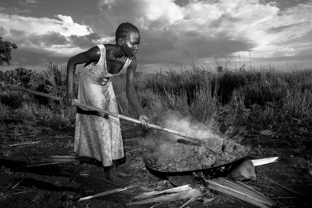 Nuer village woman cooking mash of sorghum and millet