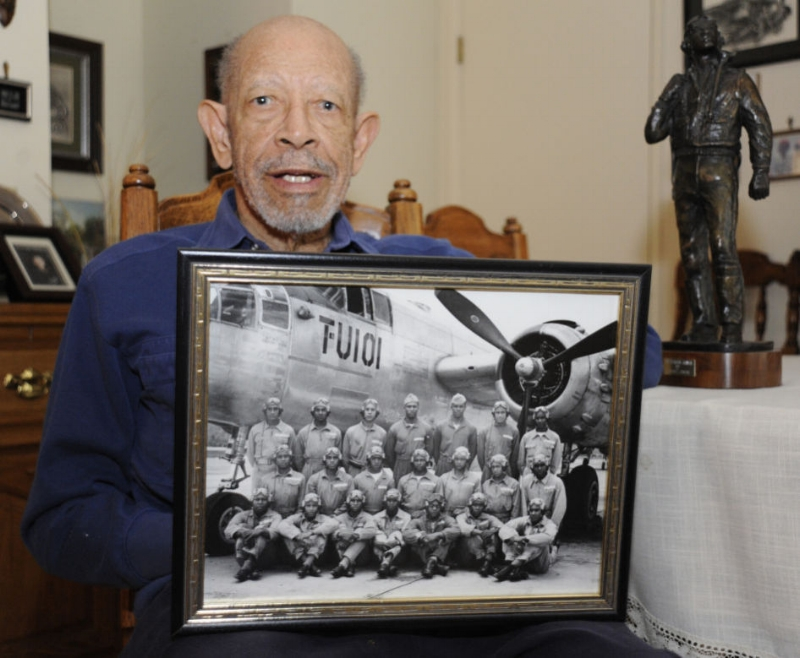 Art Hicks in 2014 holding up a photo of his pilot training class and recalling his days as a Tuskegee Airman.