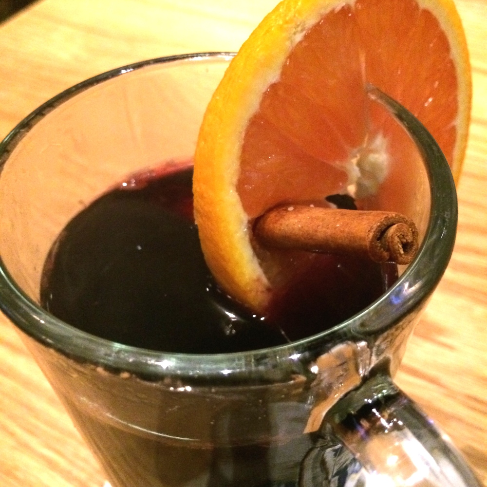 Gluwein (Warm German Christmas Wine) with a slice of orange and a cinnamon stick.