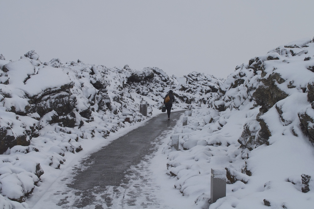 Snowy lava rock strewn walkway into the Blue Lagoon.