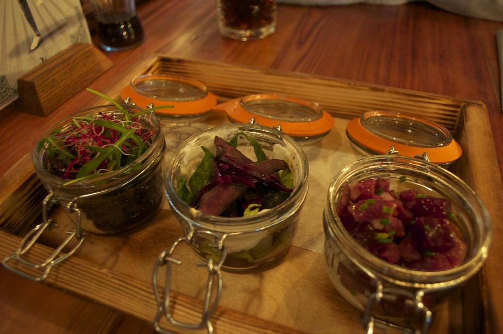 Gumbo's tray of jars - 1) Puffin, blueberry onion, lemon skyr dressing & blueberries 2) Grilled minke whale & deep fried shrimps & blueberry glaze 3) Smoked lamb tartar, beet root, onion & horseradish,