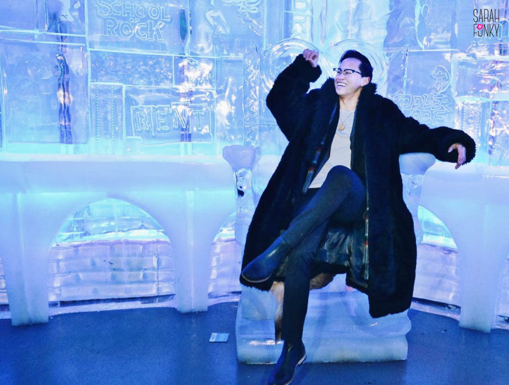 Alex sitting on the ice throne, Broadway show logos carved into the ice wall behind