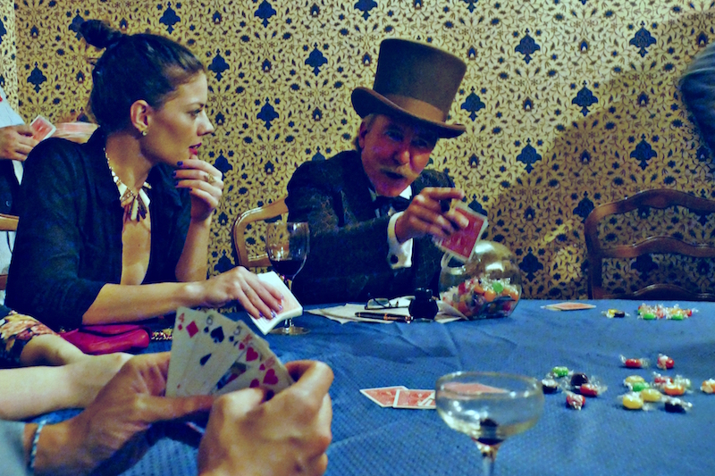A game of cards unfolds among guests and actors, the line between which frequently blurred