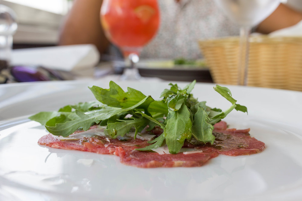 Beef Carpaccio marinated in Basil pesto, wild rocket leaves, capers, Parmesan cheese and lime