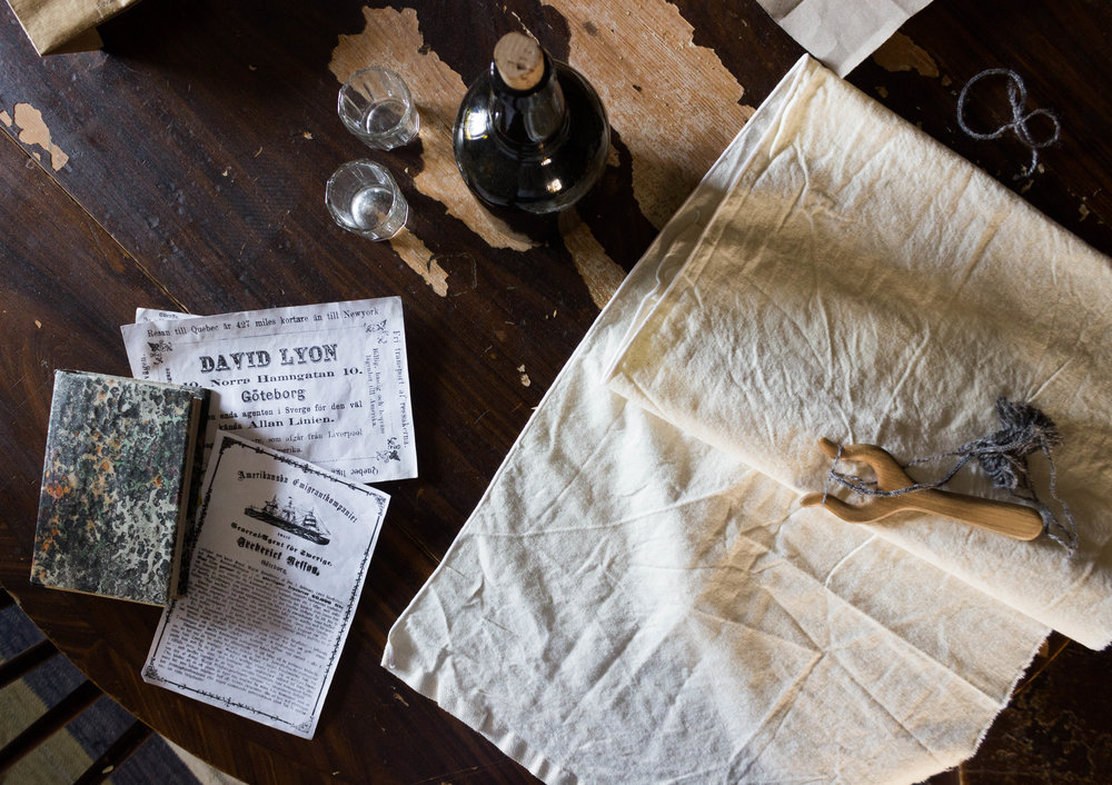A book and weaving tools lay on the table in an old cottage in Skansen