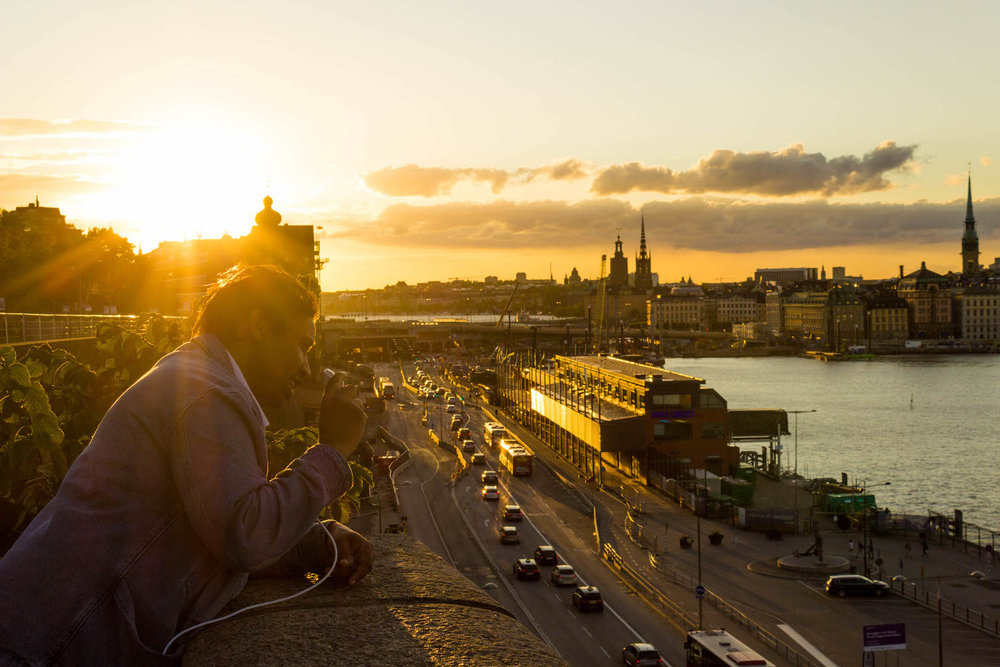 A man chats on his phone during a 10:30pm sunset - Stockholm, Sweden