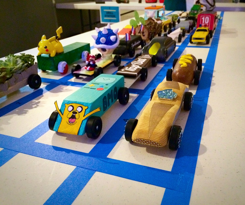 Our very first Pinewood derby car- nicknamed 'The Shiny Wedge'- is lined up with some of her contenders, which included an incredibly realistic corn dog, a Super Mario car, and a succulent planter.