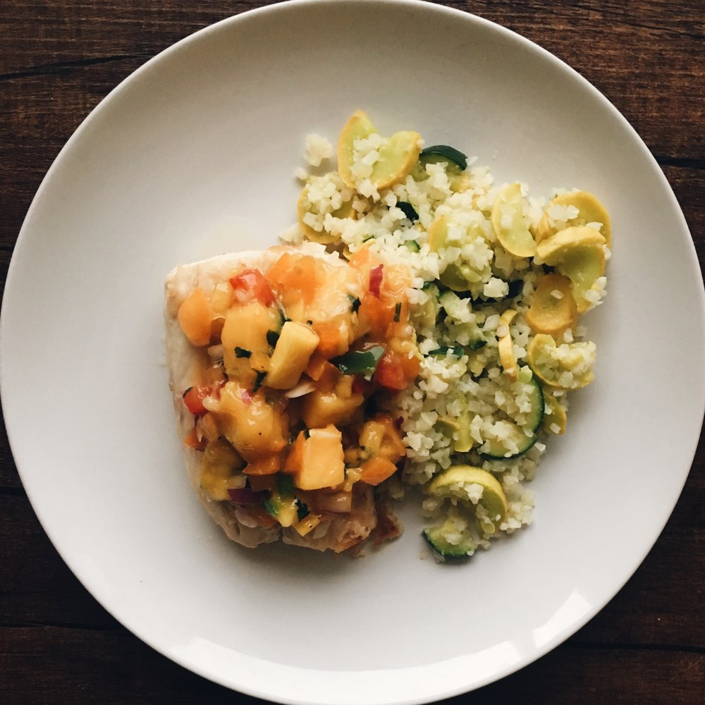 Homemade mango salsa, salmon, cauliflower rice with zucchini and squash.