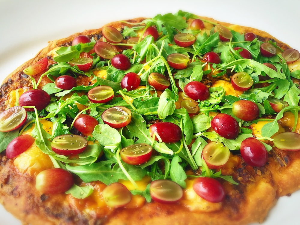 Hatch Chile Flatbread with Arugula and Grapes   Ingredients Store bought Pizza dough (to save time) 1/2 c pureed chiles (use the whole roasted chiles from last recipe) 3 tbs water 1 c shredded cheese (I used white cheddar) 1 c sliced grapes 1 c arugula leaves   Preparation 1. Mix the pureed chile with the water to make a spreadable base sauce. Top with the cheese and bake according to the directions.  2. Add the Arugula leaves and the grapes and slice immediately.