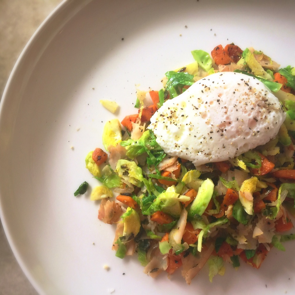 A plate of vegetable hash; topped with a poached egg.