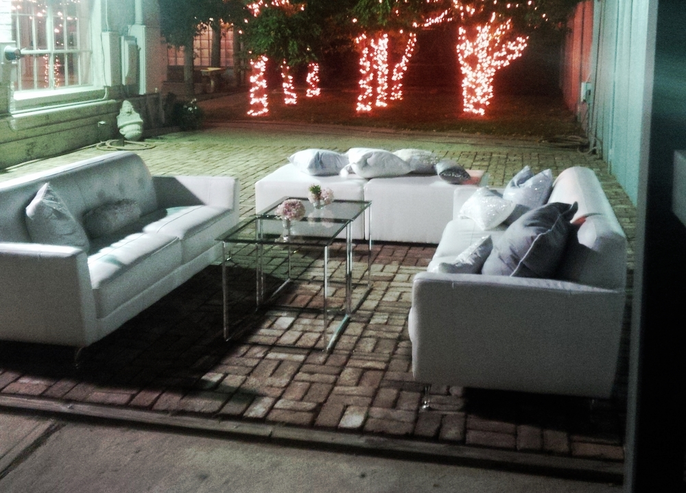 White Couches, Chrome Tables and Ottomans