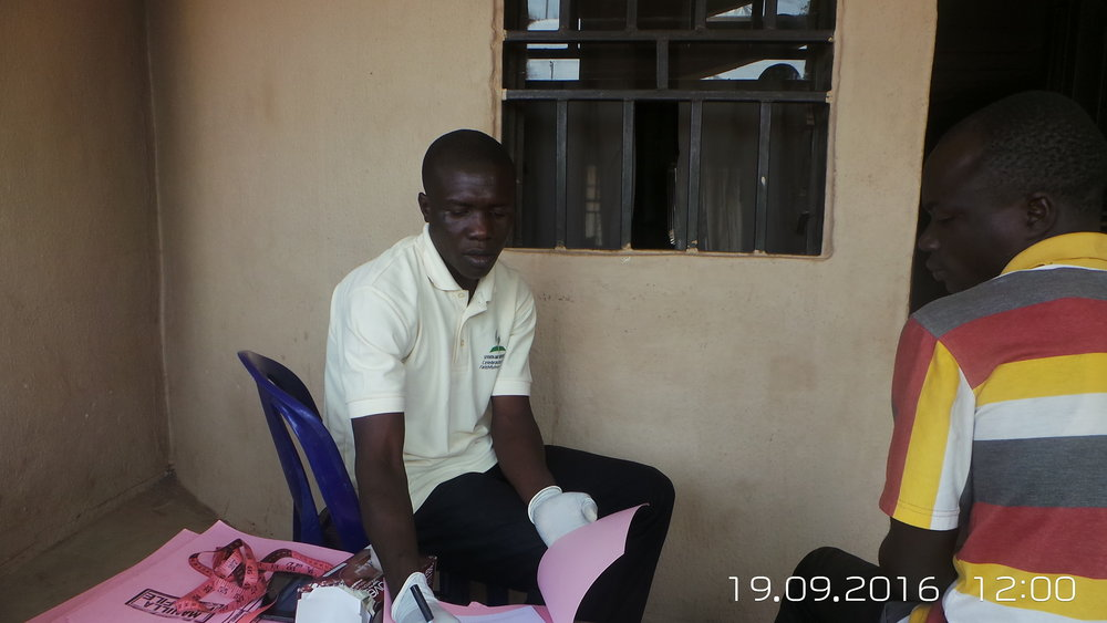 Community Based Volunteer, Matthias, taking vitals. Chief's Palace, Mararaba.