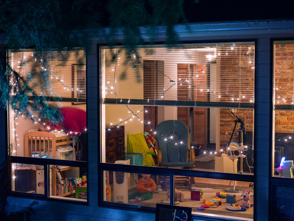 The artist's family observed through the living room window of their family home in the waning moonlight of the 2015 Winter Solstice, shot December 23rd, 2015. Photograph by Michael Clinard.