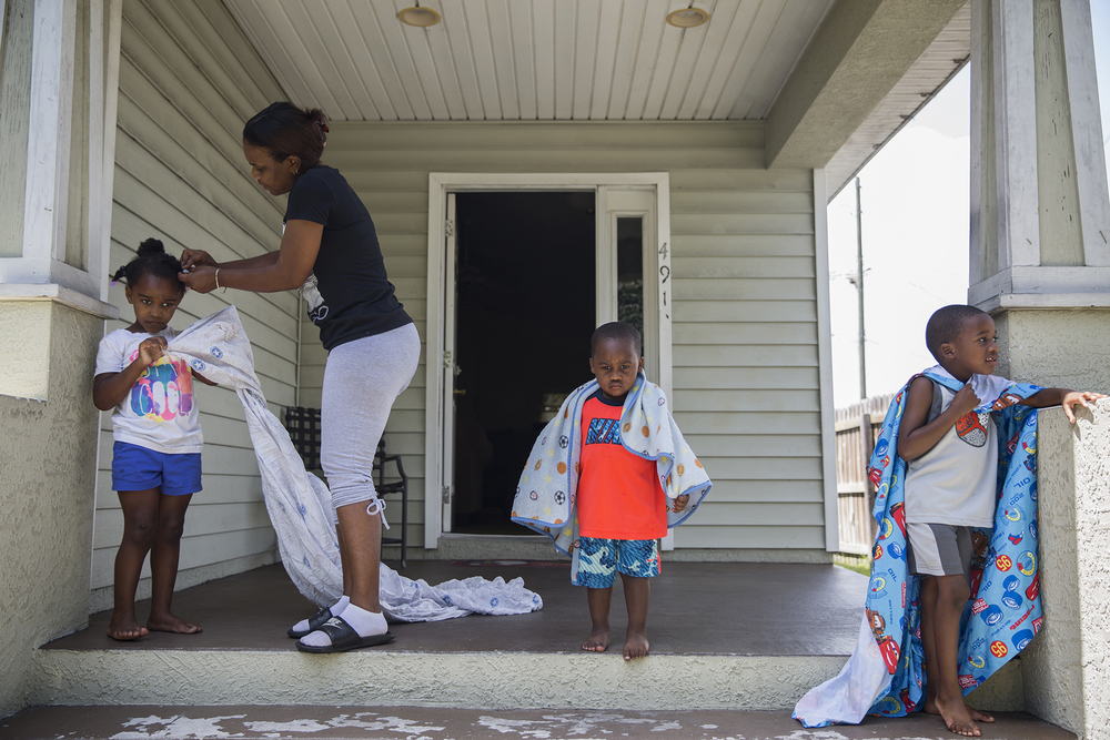 """On June 26, 2014, three of Cora Campbell's family members were killed by a hit-and-run driver. They were her daughter, Briana Campbell, niece, Jame'sia Lang, and sister, Grace Collier.Cora took in her three grandchildren: Zy'aire, 4, Zy'asia, 4, and Damaris, 2. """"Without them, me personally, I wouldn't know how to deal with the situation.""""    A year later, after running around inside their home with bed sheets as capes, the children move to the porch where the heat and sun created a sudden moment of silence,each lost in their own childlike world. Cora fixes her granddaughter Zy'asia's hair, left, with her two grandsons Damaris, center, and Zy'aire, right, on the porch of their home in Gulfport, FL. [Gulfport, FL. 2015]"""