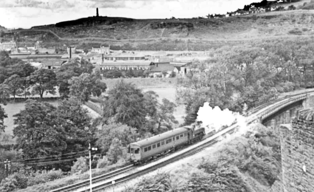 In early BR days, an autotrain drifts southwards away from Pontypridd in the direction of Upper Boat. In the background are the world famous Brown Lenox Chain Works.  The well-known photograph of IK Brunel, complete with cigar and stove-pipe hat, standing in front of the anchor chains forged for the 'Great Eastern', involved chains made in Pontypridd by Brown Lenox.   Acknowledgement: in spite of efforts made to trace its origins, this photo is by a photographer unknown.