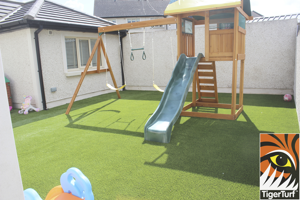 Swing set in family Garden with TigerTurf Finesse