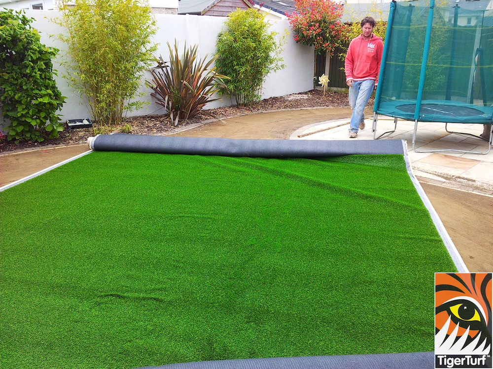 installer fitting grass around trampoline