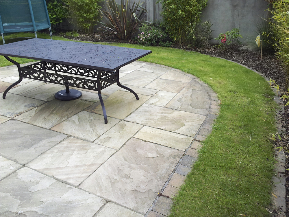Sandstone patio and curving lawn