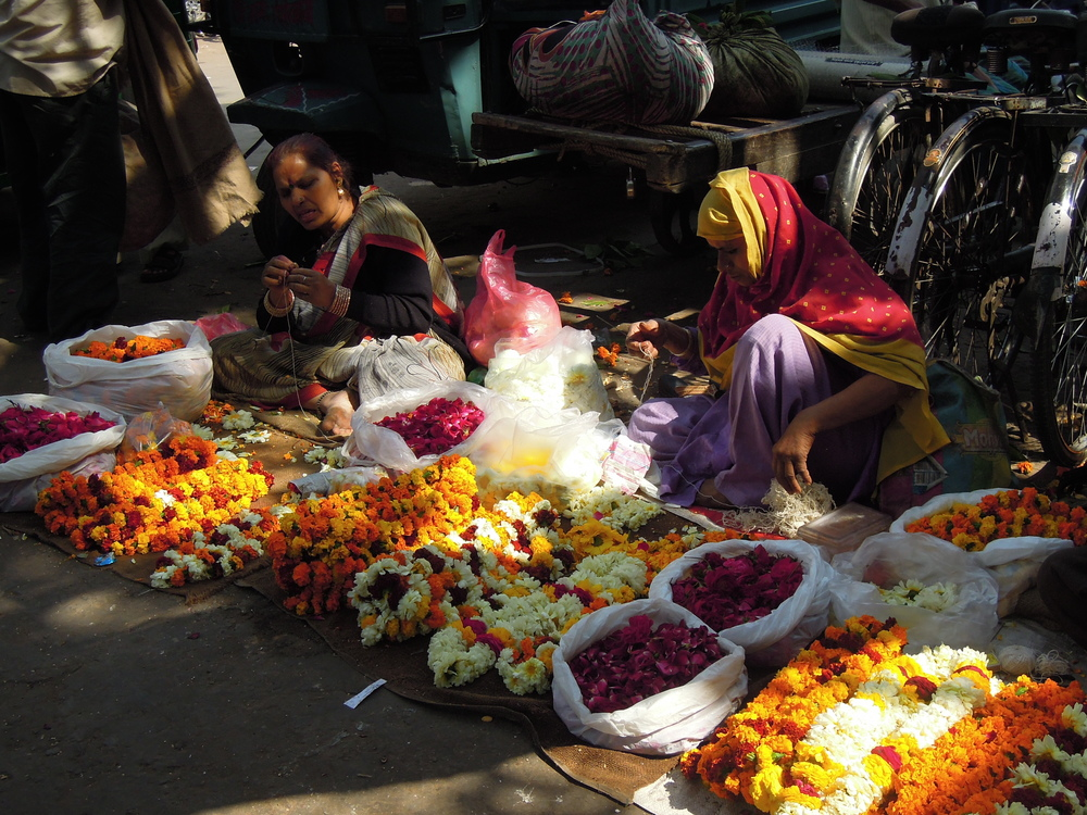 Women make and sell floral garlands by the roadside.