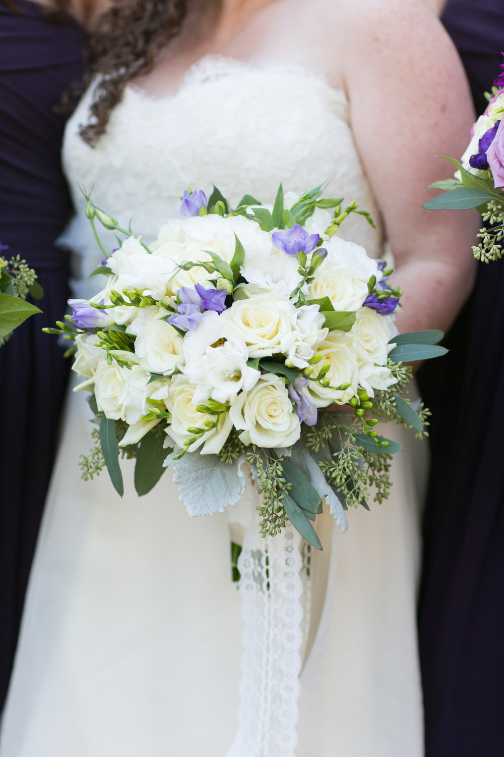 The bridal bouquet and all it's glory! Lavender Freesia, white Freesia, white roses, white Lisianthus, seeded Eucalyptus, gray Dusty Miller leaves and satin and lace ribbons.