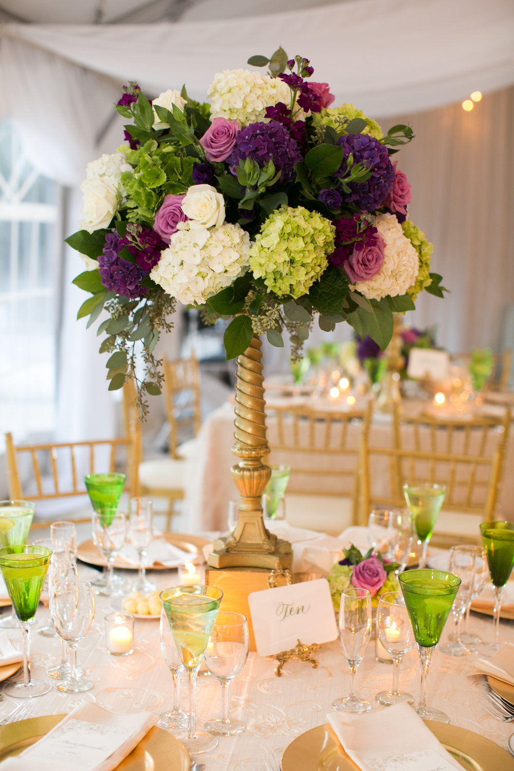 "The tent was filled with two styles of table decor - this tall centerpiece in purple, white, lavender and green with an ""old gold"" vintage riser."