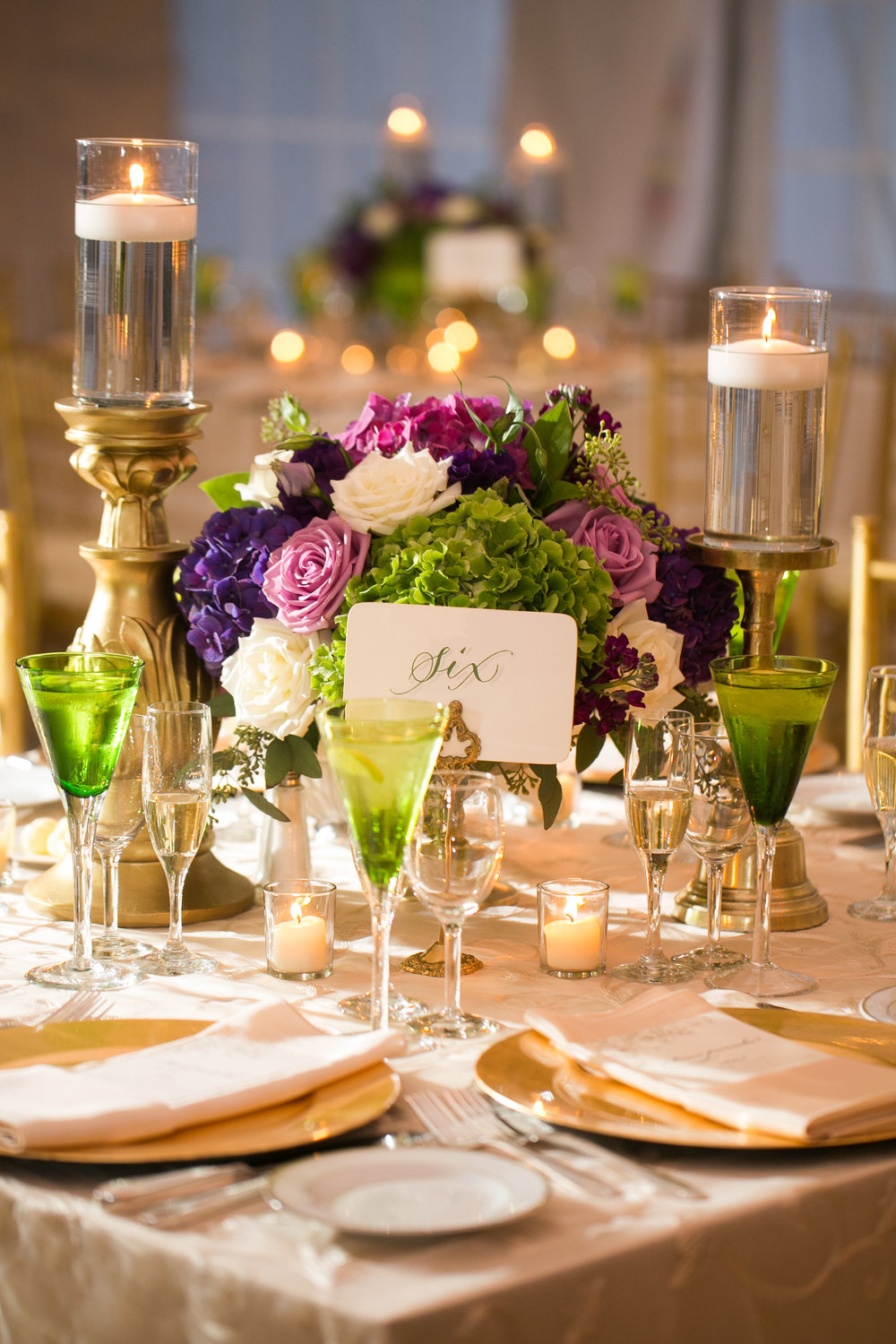 "The low centerpiece in the tent was a lush purple, green, lavender and white arrangement in a gold pedestal vase, flanked by two timeless ""old gold"" candlesticks."