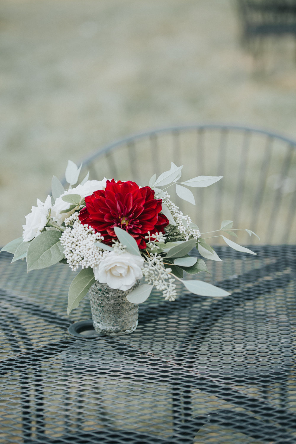 A vibrant red Dahlia on a table meant for lounging. Photography by Purple Fern.