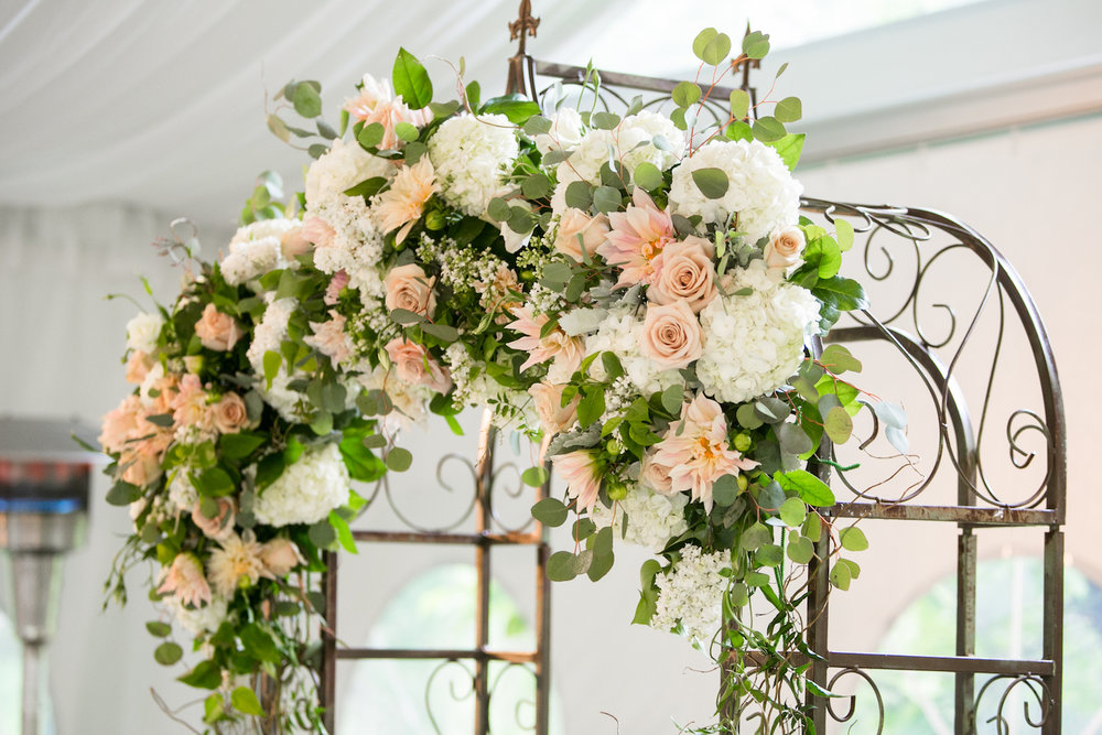 Arch flowers include Cafe Au Lait Dahlia, Quicksand Roses, White Lilac and Hydrangea, Dusty Miller, Silver Dollar Eucalyptus and Jasmine.