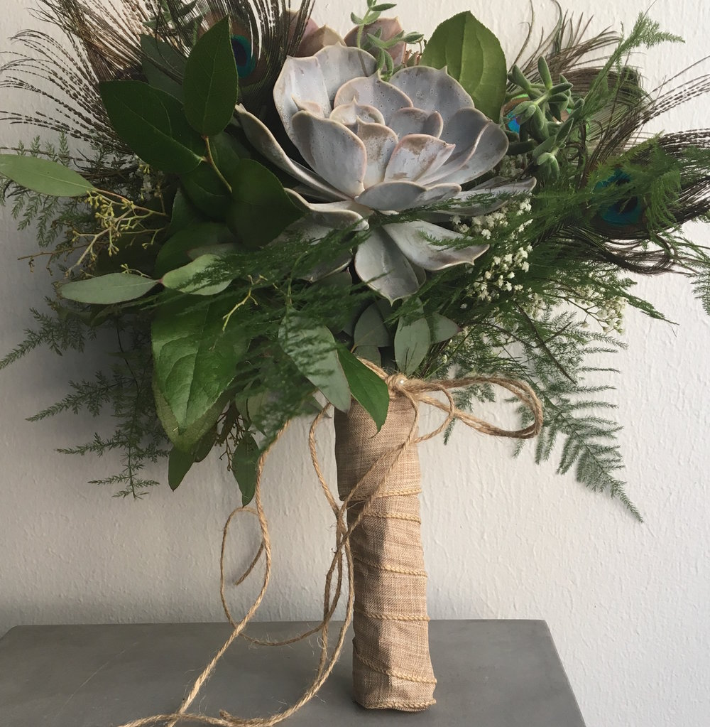 Because the Succulents and greens last out of water, we were able to use a Ballerina Wrap on the handle to hide the mechanics. This was a very popular wrap in the last decade for hand-tied bouquets.