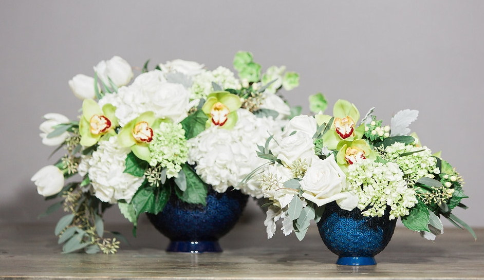 "The Pierre Compote bowl in two sizes with Hydrangea, Hellebore, Roses, Green Cymbidium Orchids and Hypericum Berry. The large one is called ""Crystal"", the medium arrangement is ""Snow."""