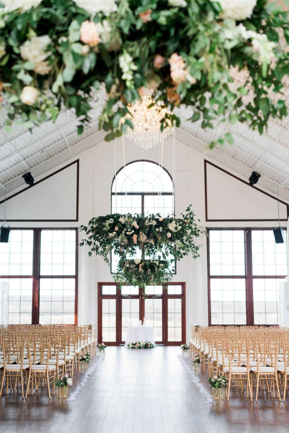 Stunning floral and greenery installations at Raspberry Plain Manor, Leesburg, Virginia in April, the beautiful chandelier at the venue is framed by our designs. The wedding party processed under the elegant installation creating a gorgeous atmosphere. Photography by Adam Mullins.