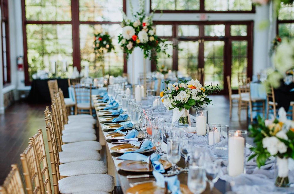 Emily Clack Photography    at    Raspberry Plain Manor   , a King's table with pillar candles in cylinders. bridesmaids bouquets and tall floral centerpieces on vintage gold plant stands.