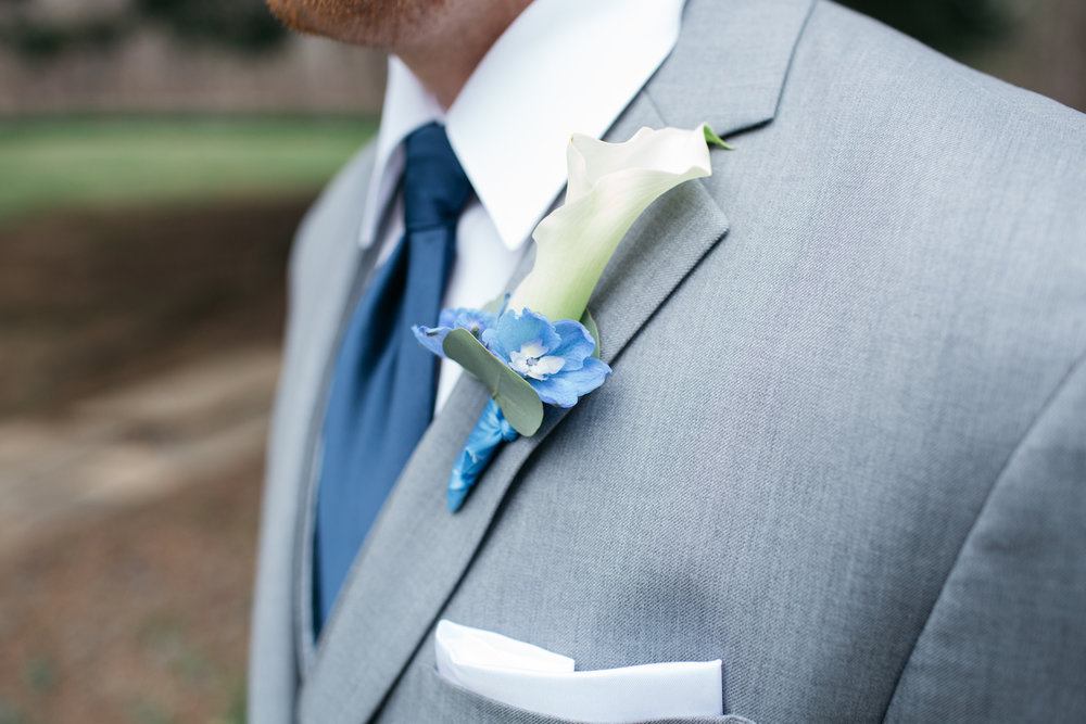 A longer thinner boutonniere with Calla Lily and Blue Delphinium. Fisher Photography.