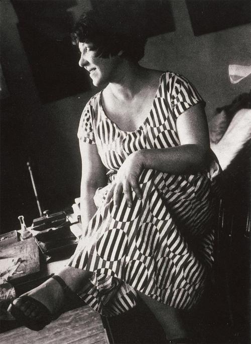 Varvara Stepanova wearing a dress made of fabric produced to her design , 1924.
