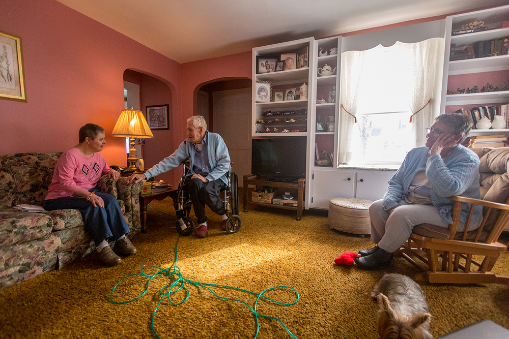 Rollin Lane, 88, sits with Kim, left, his 57-year old daughter with Down Syndrome, and Kris Zamora, right, in his Leominster home. After caring for Kim for her entire life, Rollin's declining health has forced him to seek assistance with caring for Kim.