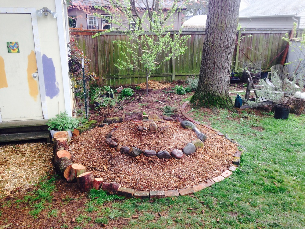 Step 3: Add wood chips and create a mounded spiral with rocks, logs, bricks, etc.