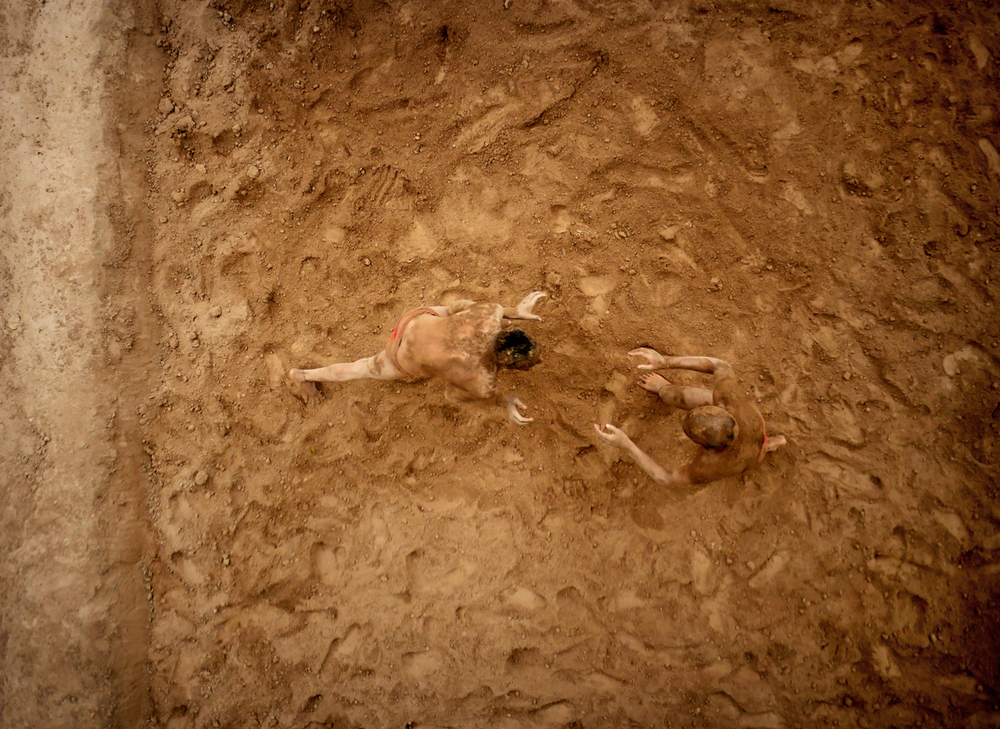 Two wrestlers practising the ancient Indian sport of Kushti in a pit they had hacked into the ground two hours earlier.