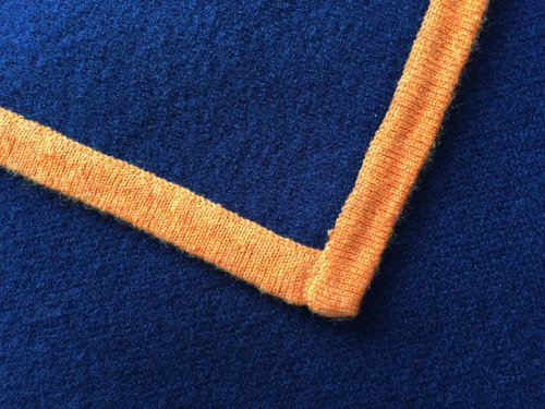 Cashmerepledd. mørkeblått med orange kontrastsøm, kr 1.250