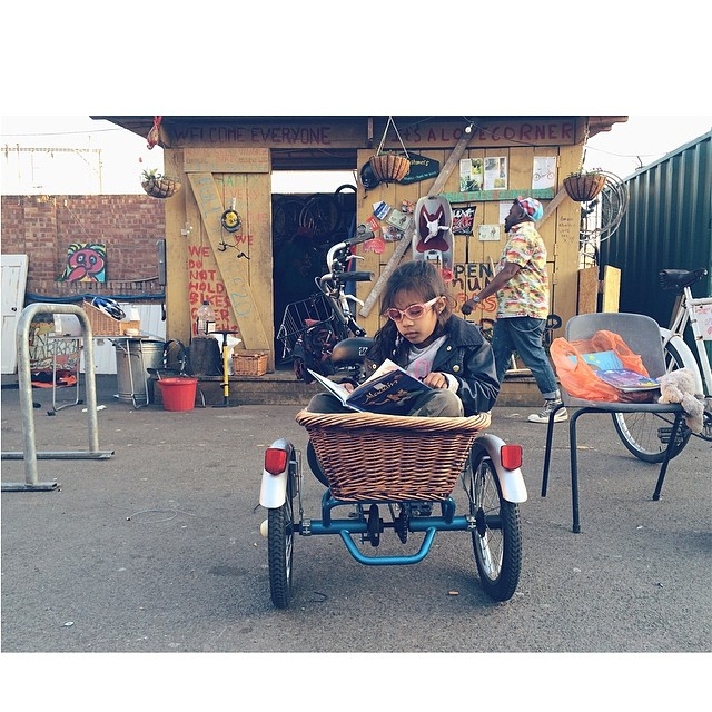 Sitting in a basket on the back of a souped up tricycle, reading a book, with your shades on. Doesn't get much cooler. #East #London #CoolKids (at Netil Market)