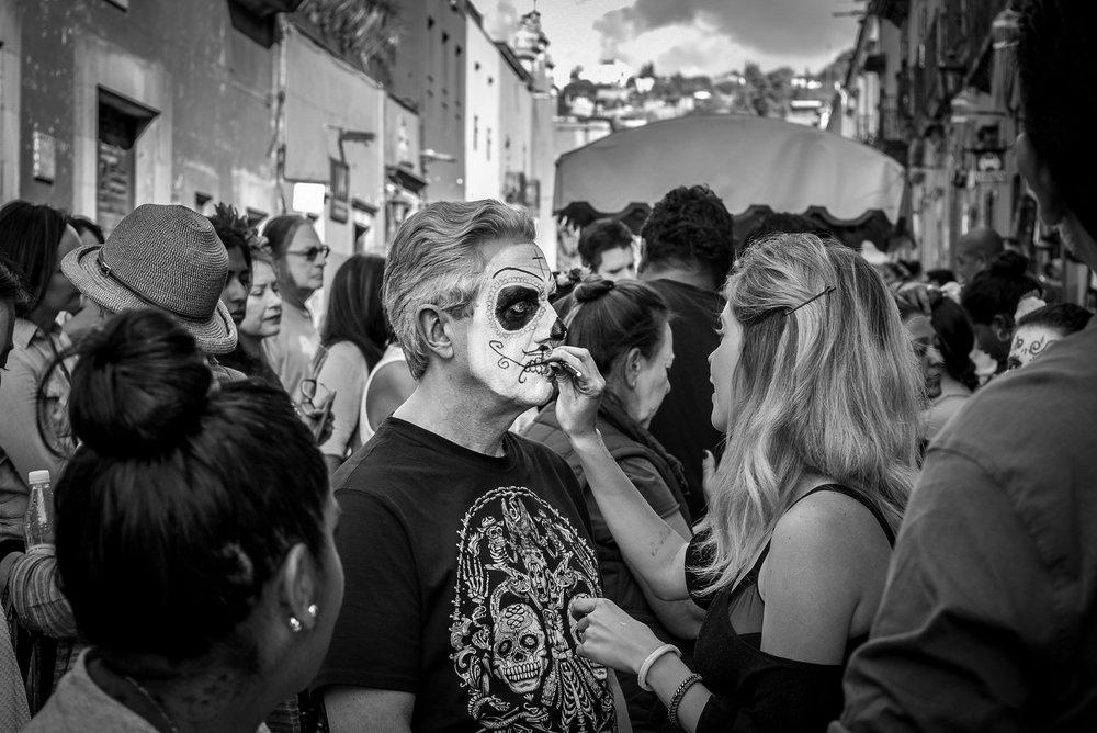 Face painting skulls in San Miguel de Allende during Dia de los Muertos
