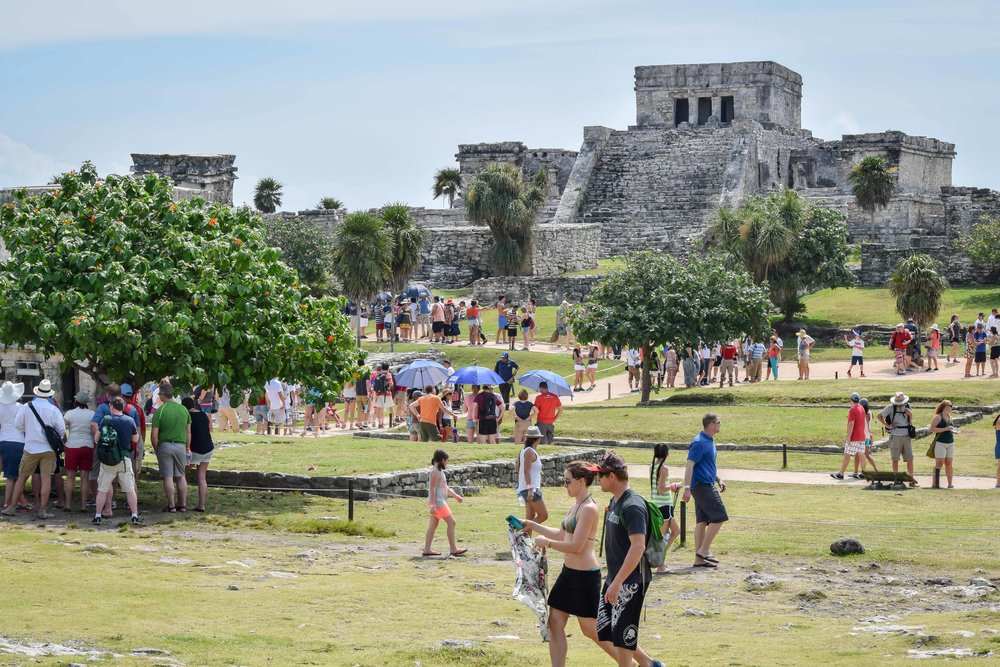 Tourists walking among the ruins of Tulum
