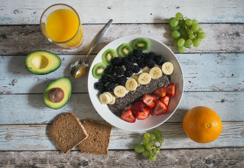 Bowl of fresh fruit, juice, and multigrain bread