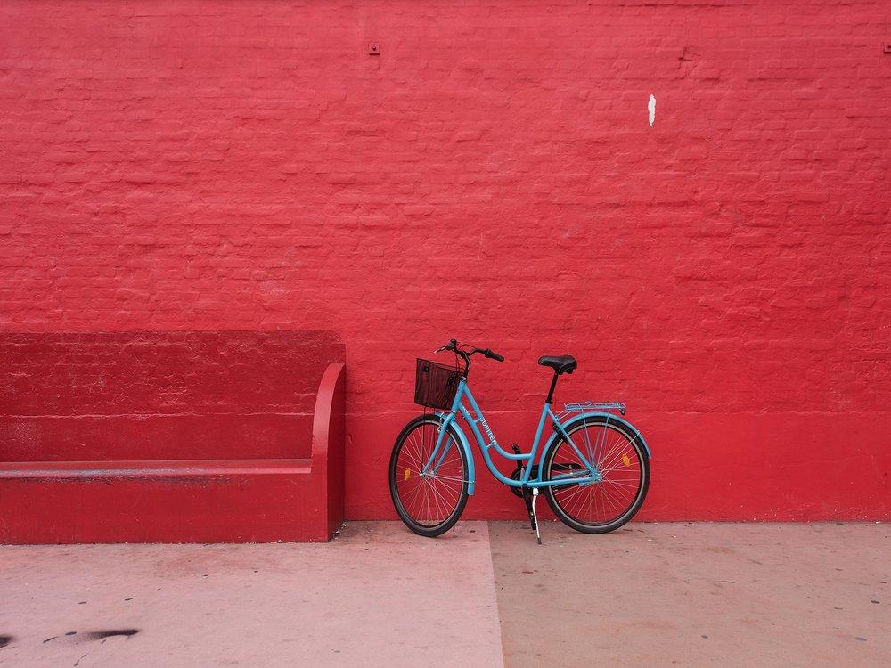 Blue bicycle against a red wall