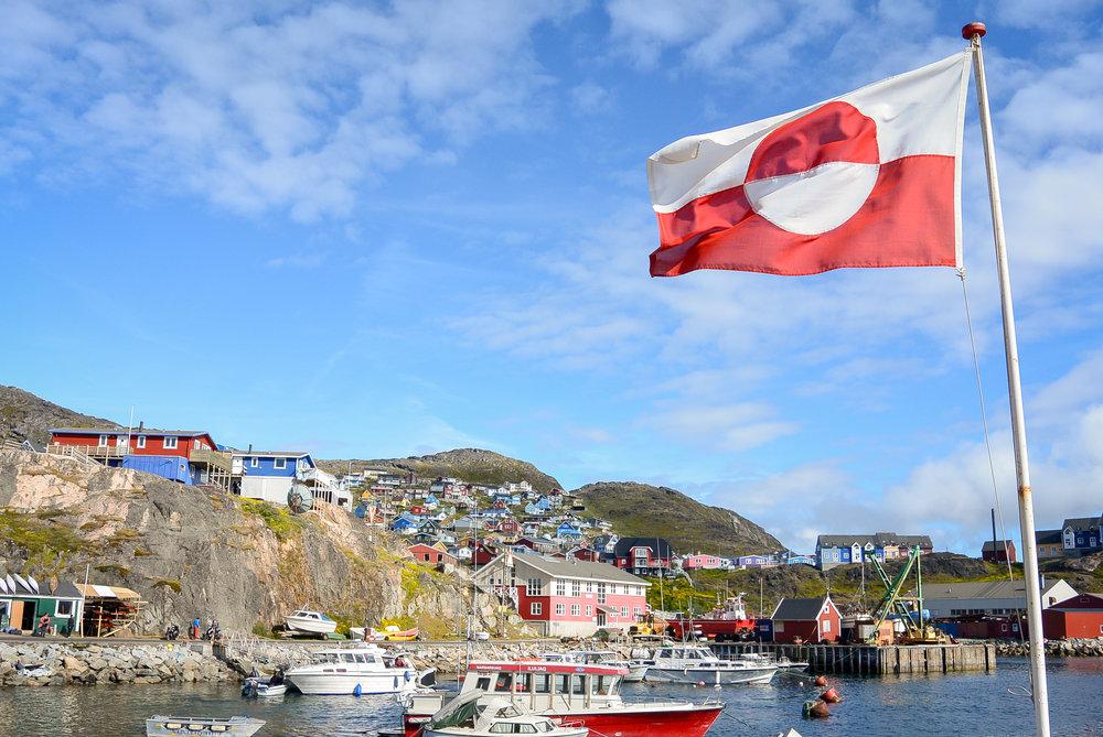 Flag of Greenland and colorful houses of Qaqortoq