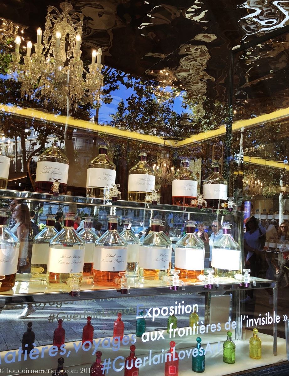 """Vitrine de la boutique Guerlain des Champs-Elysées annonçant l'exposition """"Matières, voyages aux frontières de l'invisible"""""""
