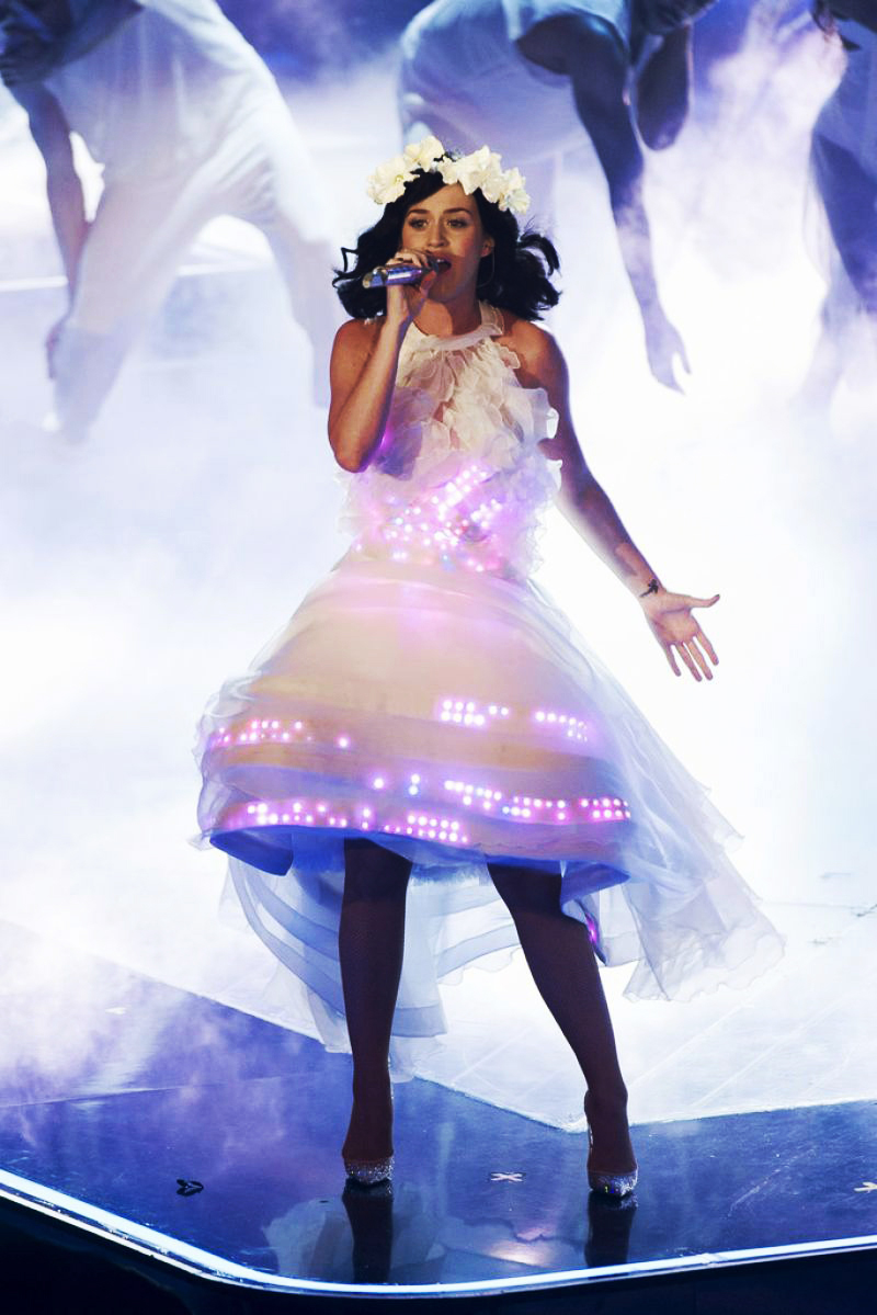 American singer Katy Perry wears a white chiffon and organza dress from CuteCircuit, while playing her title Unconditionally, on the stage of The Voice of Germany, on December 13, 2013, in Berlin. CuteCircuit is an English fashion tech brand, created by designers Francesca Rosella and Ryan Genz, specialized in wearable and interactive fashion.