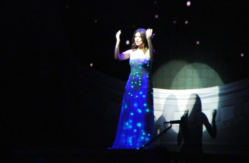 Laura Pausini sings Invece no, during her world tour Inedito, in the Arena of Verona, on June 4, 2012. The Italian singer wears a CuteCircuit dress called Aqua Dress, composed of 5670 leds and Swarovski crystals on black tulle.