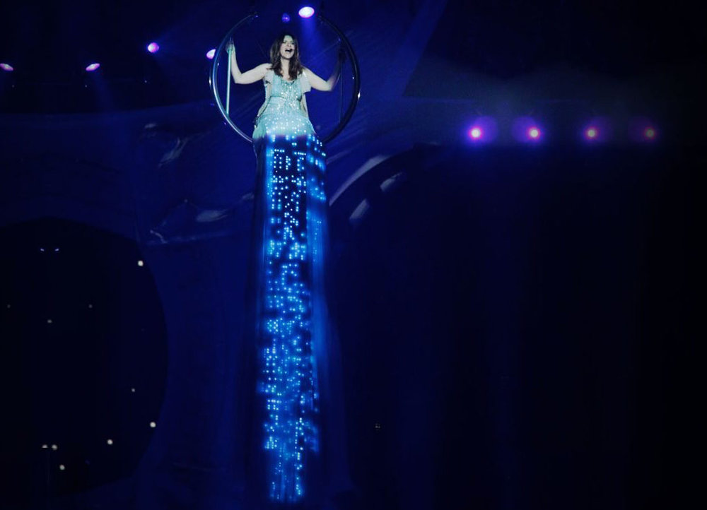 Laura Pausini sings Invece no, during her world tour Inedito, in Milan, on December 22, 2011. The Italian singer wears a CuteCircuit skirt of 45 meters of chiffon incorporating thousands of leds and Swarovski crystals.